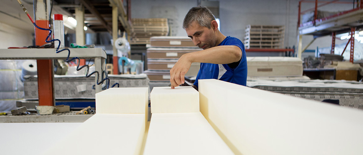man pressing down on mattress foam inside factory
